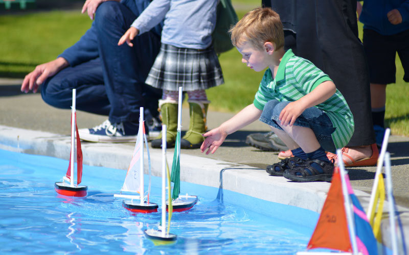 Young child playing with sailing boat toys in pool.