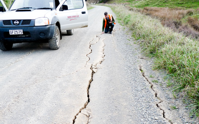 Council staff assess earthquake damage to road.