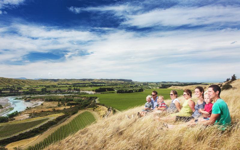 Family sitting on hillside in Seddon.