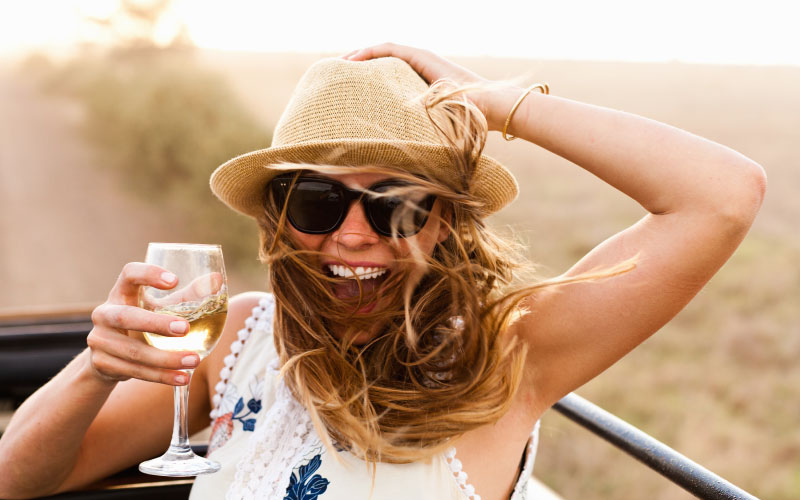 Woman smiling in summer time with wine glass.